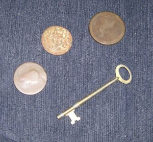 3 discolored metal discs & Brass Key