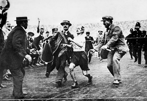 ORIGINAL CAPTION: Sir Arthur Conan Doyle, right, gives Dorando Pietri an assist across the finish line. 2016 COMMENT: That's not ACD in the photo!